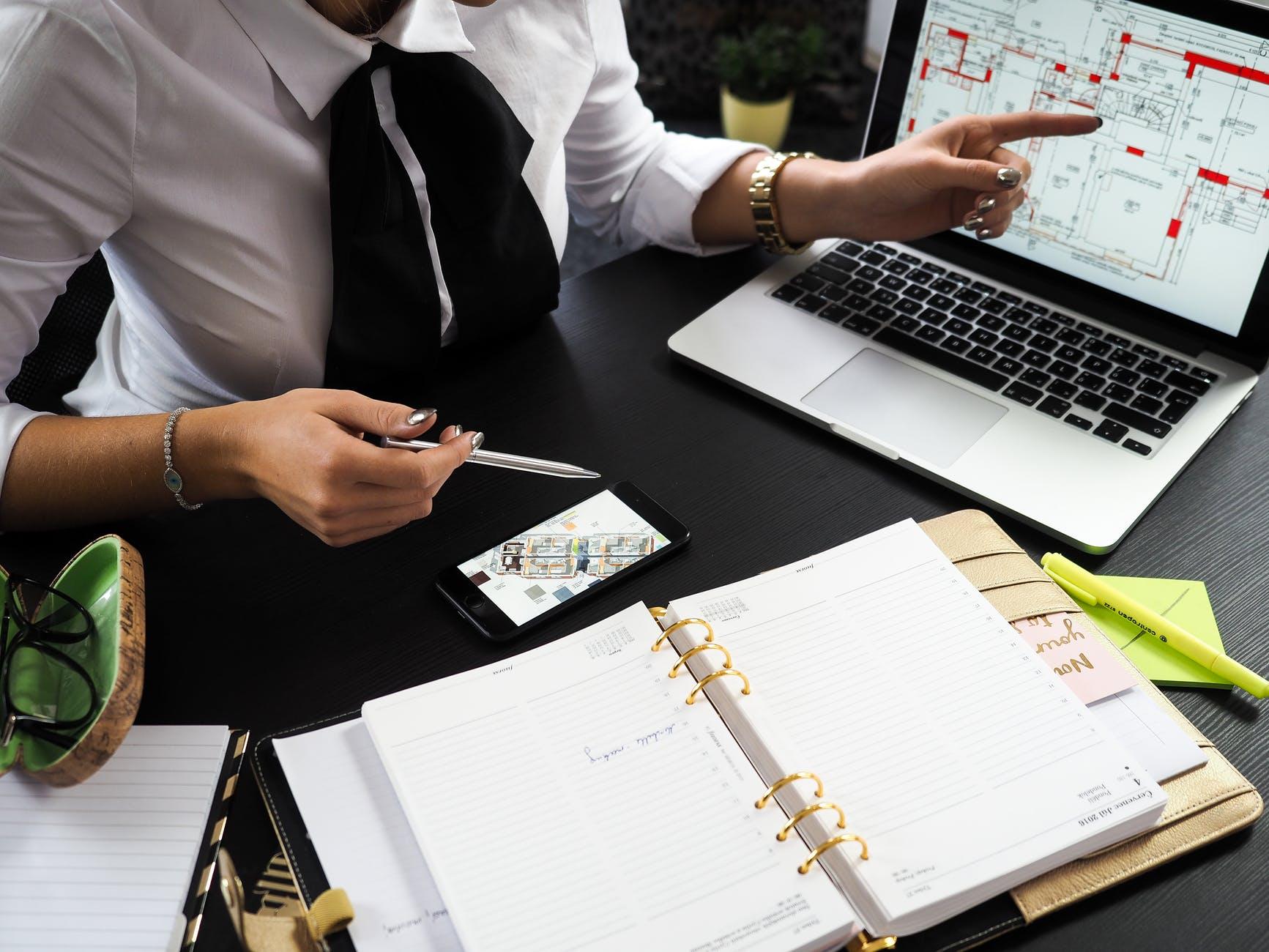 person holding gray pen sitting near laptop